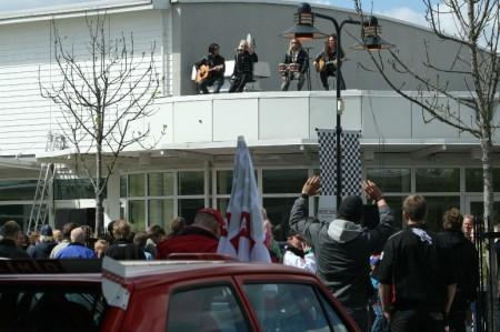 The Poodles uppträder på taket ovanför Dream Car Rental